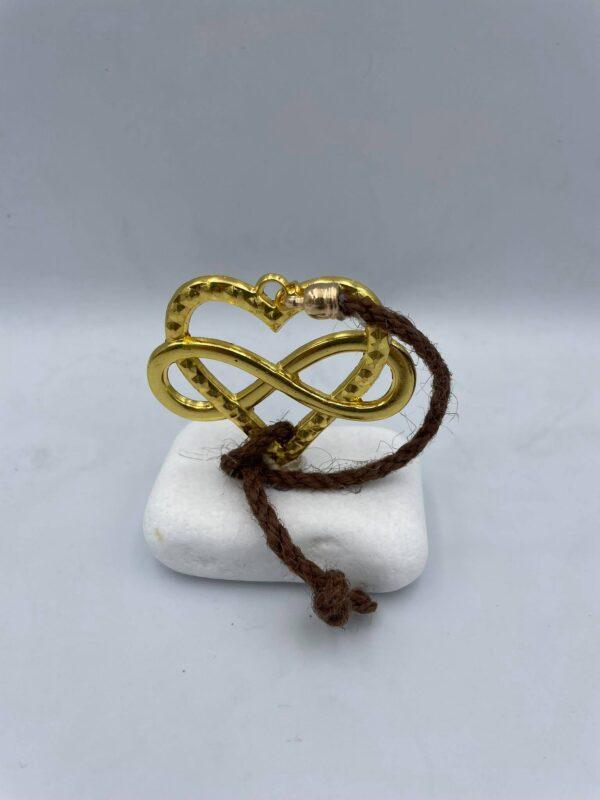 Καρδιά σε χρυσαφί χρώμα με το σύμβολο infinity και κορδονάκι πάνω σε βότσαλο
