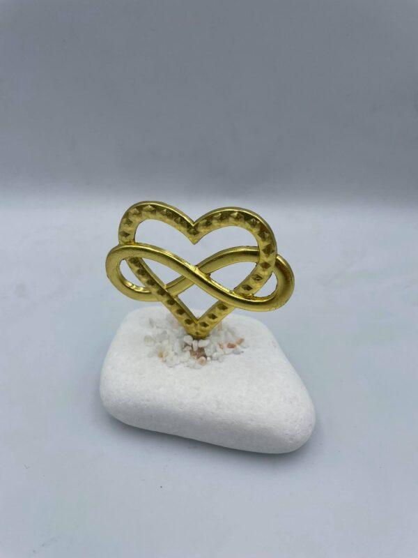 Καρδιά σε χρυσαφί χρώμα με το σύμβολο infinity πάνω σε βότσαλο