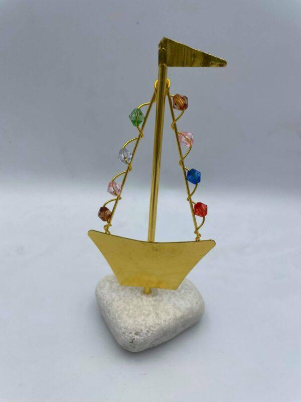 Καράβι σε χρυσαφί χρώμα με χαντρούλες πάνω σε βότσαλο